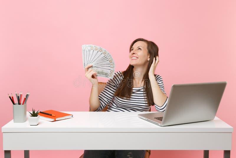 Mirada de pensamiento sonriente soñadora joven de la mujer que detiene porciones del paquete de los dólares, trabajo del dinero d fotos de archivo libres de regalías