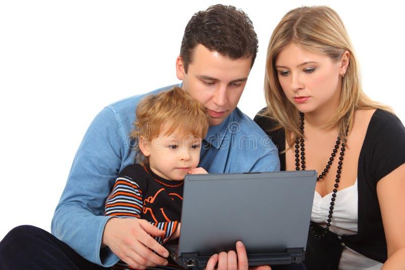 Mirada del hijo de la pizca de los padres en el cuaderno imagen de archivo libre de regalías