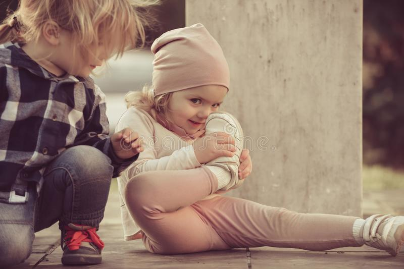 Mirada del muchacho en la nariz del tacto de la muchacha con el zapato del deporte imagen de archivo libre de regalías