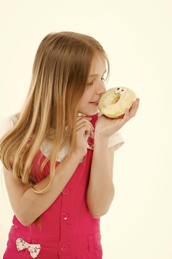 Mirada del niño en el buñuelo en blanco Ni?a con el bu?uelo esmaltado del anillo Ni?o con la comida basura Consumici?n malsana y fotos de archivo libres de regalías