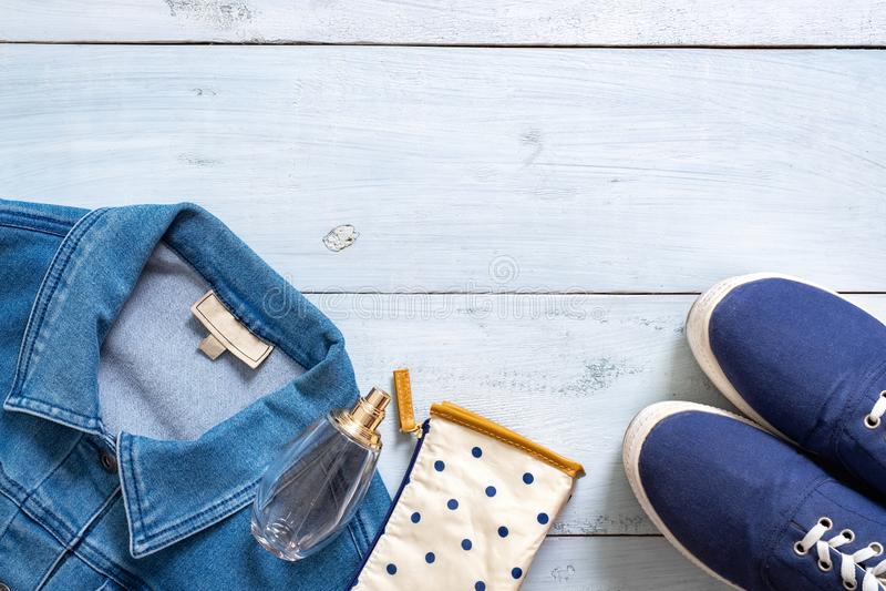 Mirada elegante de la ropa en estilo puesto plano en el escritorio de madera coloreado en colores pastel azul imagenes de archivo
