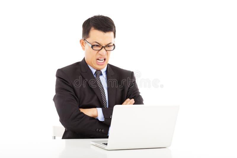 Mirada enojada del hombre de negocios en los brazos del ordenador portátil y de la cruz fotos de archivo