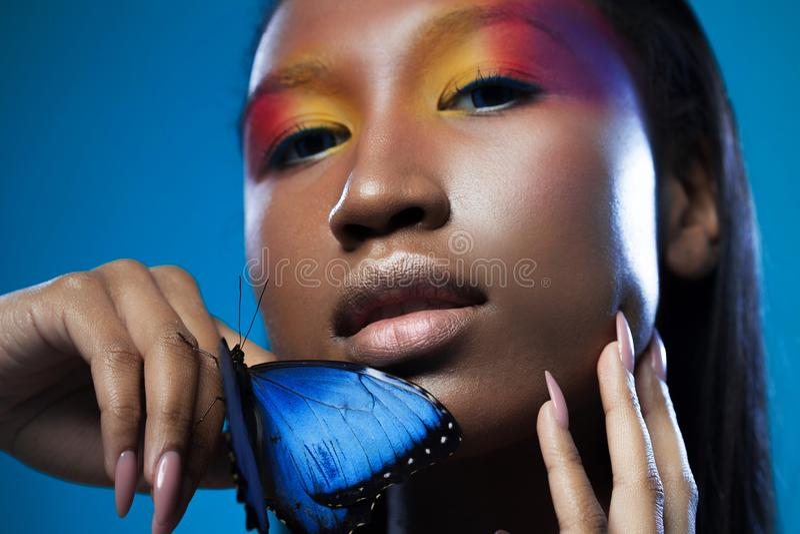 Mirada exótica modelo negra joven y hermosa con la mariposa azul brillante fotografía de archivo