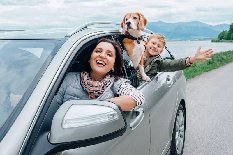 Mirada feliz de la familia hacia fuera de las ventanillas del coche fotos de archivo libres de regalías