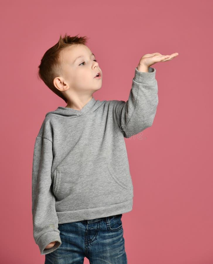 Mirada feliz del niño del bebé del niño para arriba con la mano abierta de la palma para el concepto del espacio del texto de la  fotos de archivo libres de regalías