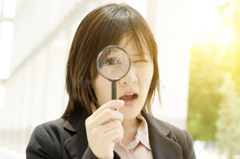 Mirada femenina asiática a través del vidrio de la lupa foto de archivo
