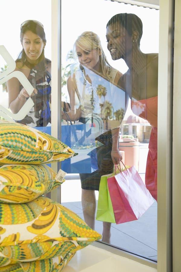 Mirada femenina de los compradores en los amortiguadores a través de la ventana de la tienda fotos de archivo
