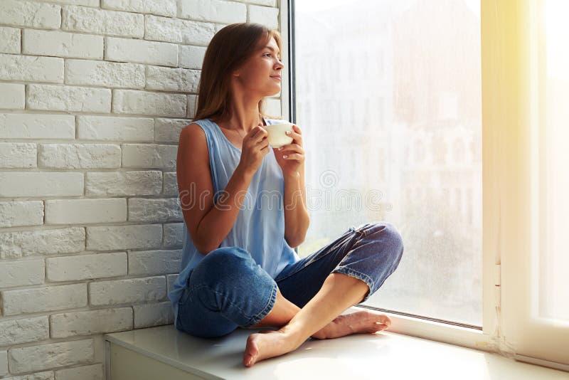 Mirada femenina joven contenta e inspirada a través de la ventana fotos de archivo libres de regalías