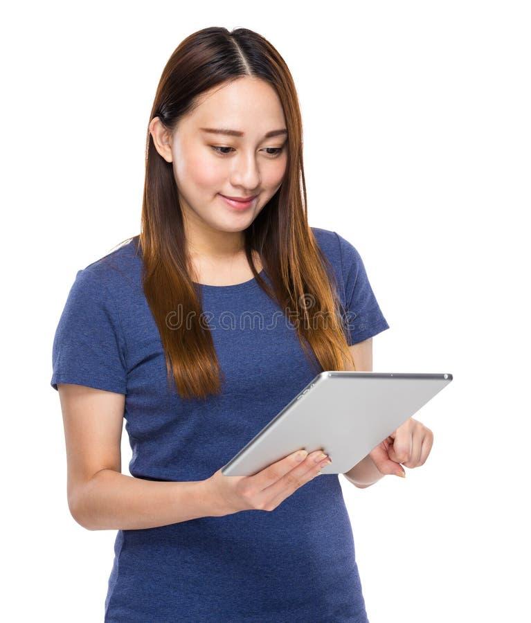 Mirada indonesia de la mujer de la raza mixta en la tableta digital fotos de archivo libres de regalías