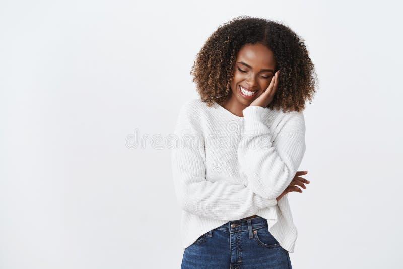 Mirada linda de ruborización de risa encantadora del peinado rizado afroamericano despreocupado divertido de la mujer abajo del t imagen de archivo