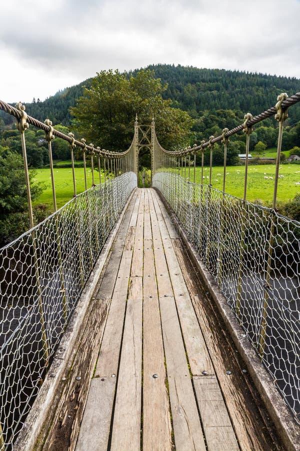 Mirada a lo largo de la calzada de madera de puente colgante imagenes de archivo