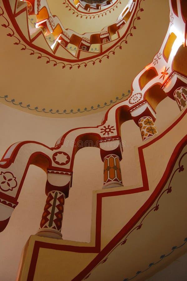 Mirada para arriba de la escalera con diversos símbolos en la barandilla fotos de archivo