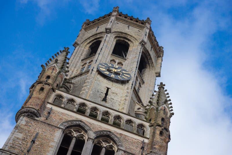 Mirada para arriba de la vista del campanario medieval de Belfort del campanario con el reloj de la torre y el cielo nublado Beli imagen de archivo libre de regalías
