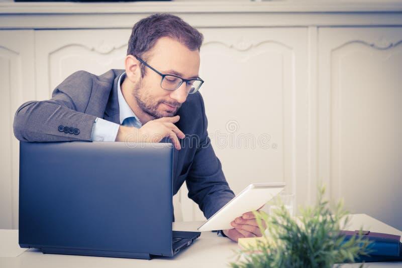Mirada profesional joven en el dispositivo de la tableta y el inclinarse en lapto imagenes de archivo