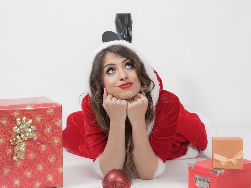 Mirada propensa de mentira de la mujer pensativa de Papá Noel para arriba con la cabeza que descansa sobre las manos y los regalo imágenes de archivo libres de regalías