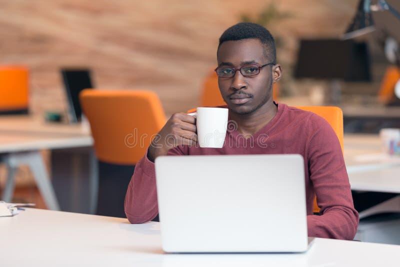 Mirada que mecanografía del hombre de negocios africano joven alegre en el ordenador portátil imagenes de archivo