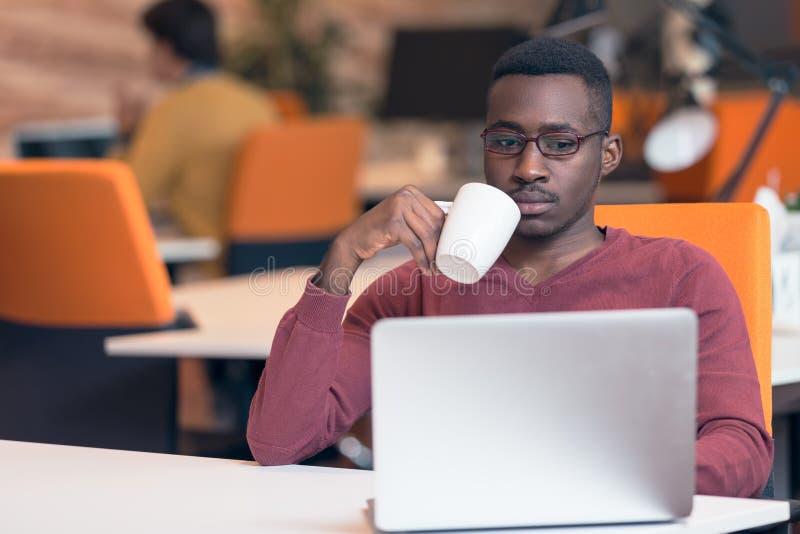 Mirada que mecanografía del hombre de negocios africano joven alegre en el ordenador portátil imagen de archivo
