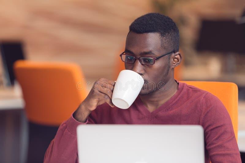 Mirada que mecanografía del hombre de negocios africano joven alegre en el ordenador portátil fotos de archivo