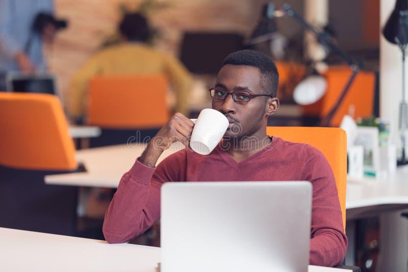 Mirada que mecanografía del hombre de negocios africano joven alegre en el ordenador portátil imagen de archivo libre de regalías