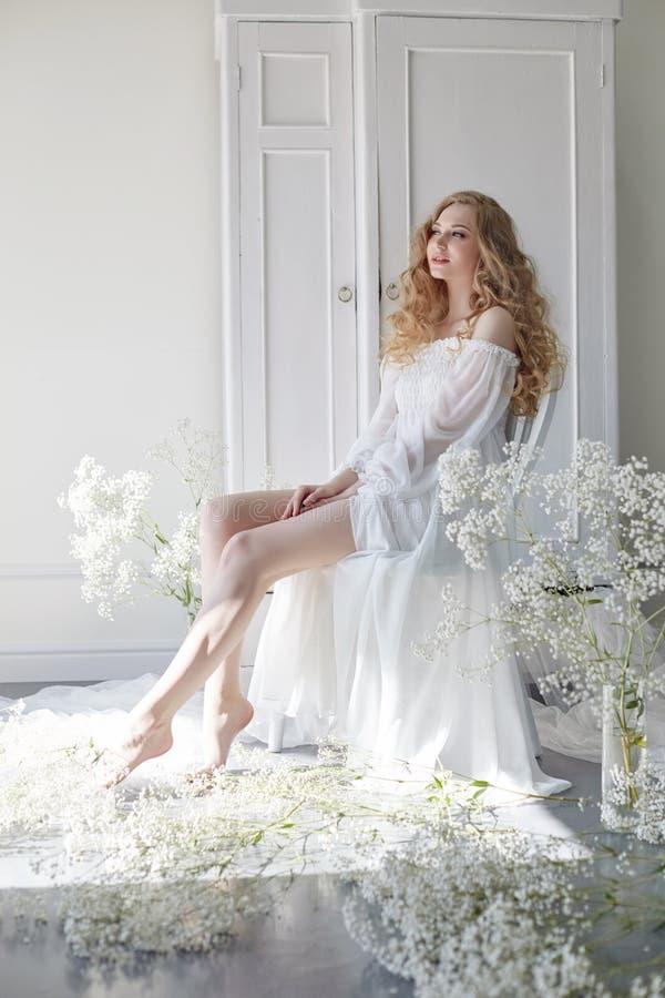 Mirada romántica rubia rizada, ojos hermosos Wildflowers blancos en manos Vestido y pelo rizado, retrato de la luz blanca de la m foto de archivo