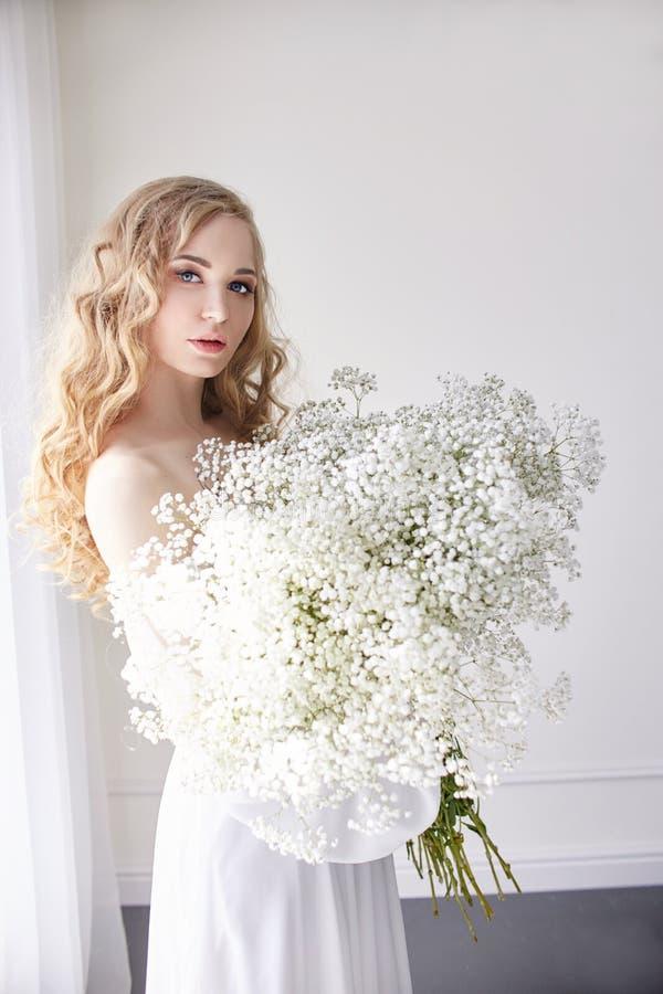 Mirada romántica rubia rizada, ojos hermosos Wildflowers blancos en manos Vestido y pelo rizado, retrato de la luz blanca de la m fotografía de archivo