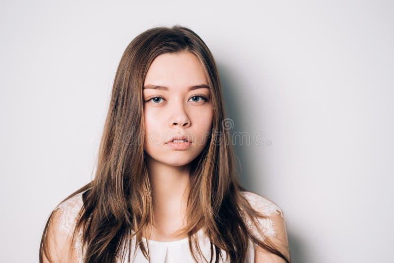 Mirada seria y en cuestión de la mujer triste hermosa joven imagenes de archivo