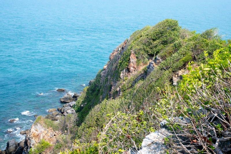 Mirada sobre un borde del acantilado con el mar azul abajo y borde del acantilado y el mar Liso gastado de las piedras a lo largo imagen de archivo libre de regalías