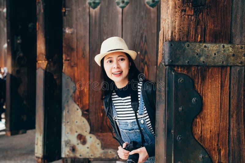 Mirada sonriente de la muchacha curiosa de puerta de madera fotografía de archivo