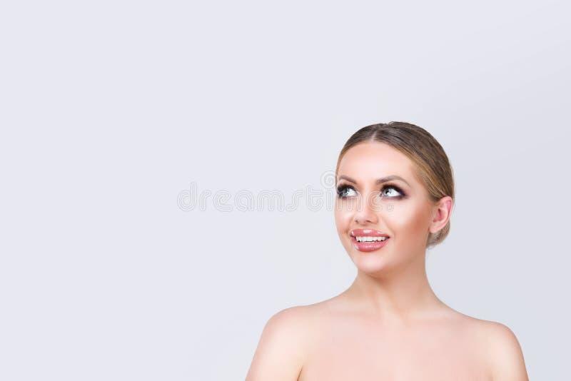 Mirada sonriente de la mujer morena joven para arriba al lado fotos de archivo