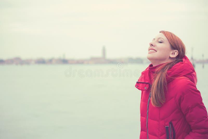 Mirada sonriente de la mujer para arriba al cielo que disfruta de la libertad en una ciudad del fondo de Venecia Italia foto de archivo