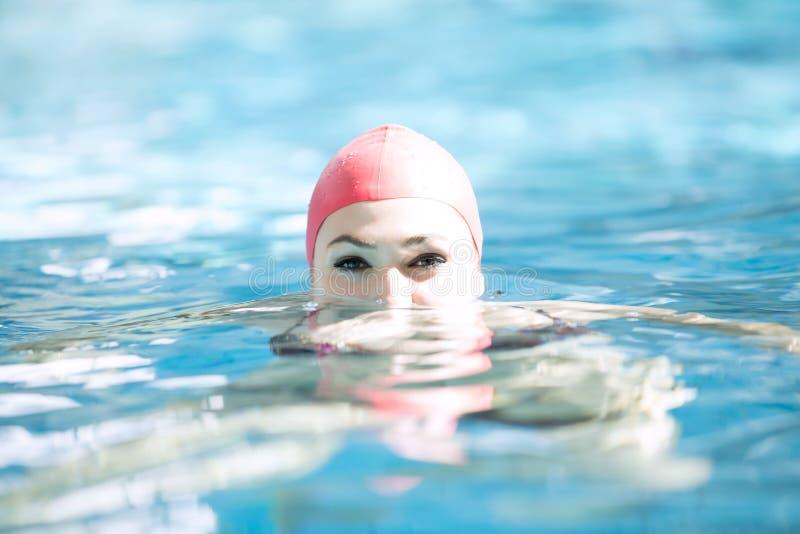 Mirada sonriente del casquillo hermoso de la mujer a la cámara en la frontera de la piscina fotografía de archivo
