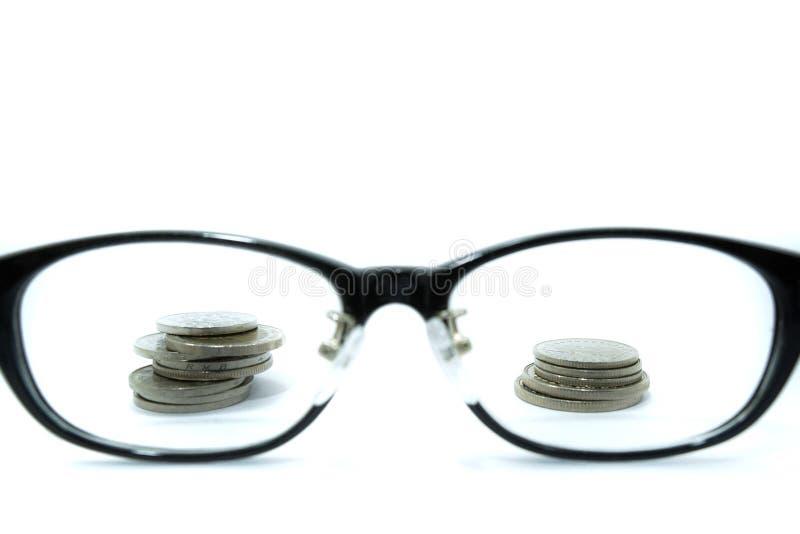 Mirada todo al dinero Meta del concepto a rico monedas y vidrios aislados en el fondo blanco imagen de archivo