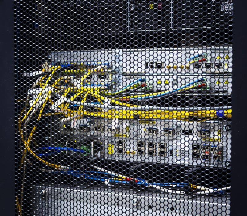 Mirada a través de puertas del modelo del panal dentro del estante grande moderno del servidor de datos en centro de datos con ha fotos de archivo