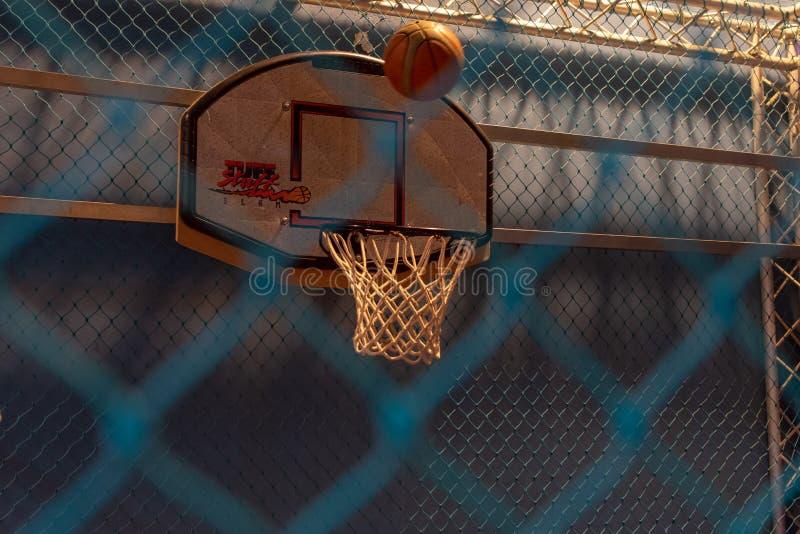 Mirada a través de una cerca azul a una cancha de básquet interior con un baloncesto alrededor para anotar una cesta foto de archivo libre de regalías