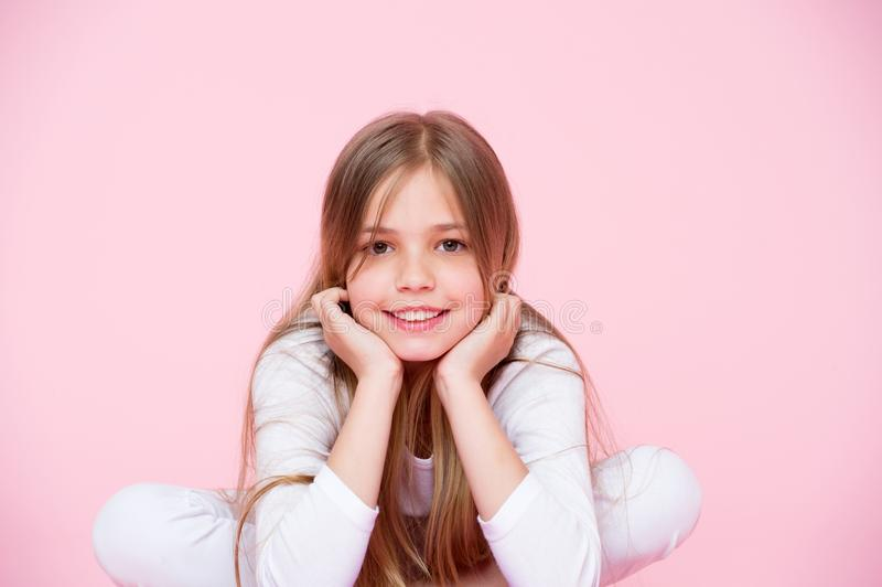 Mirada y cuidado del cabello, pastel dinámico de la belleza Fondo del rosa de la sonrisa de la niña Niño feliz con la cara linda  foto de archivo