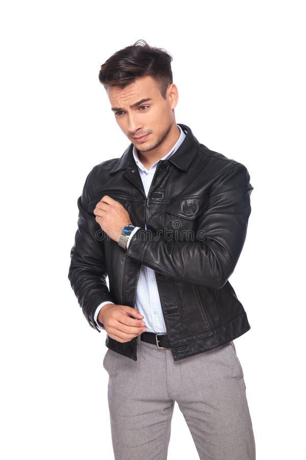Miradas de la chaqueta de cuero del hombre de negocios que llevan atractivo abajo a echar a un lado imagen de archivo libre de regalías