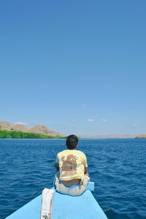 Miradas detrás de un hombre joven que se sienta en una nave en el mar alrededor de la isla de Komodo imágenes de archivo libres de regalías