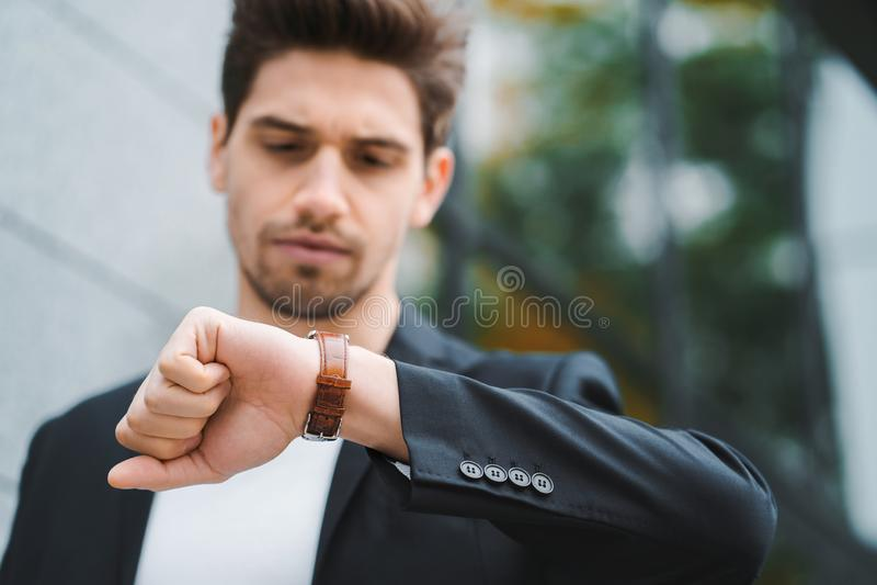 Miradas hermosas del hombre de negocios o del estudiante en el reloj Hombre joven en prisa tarde para el trabajo Modelo masculino imagen de archivo libre de regalías
