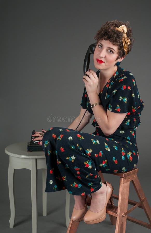 Miradas modelas de la muchacha exasperadas mientras que en el teléfono viejo imagen de archivo libre de regalías