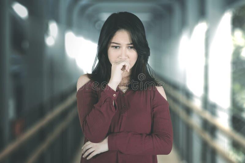 Miradas tristes de la mujer confusas en el puente peatonal imagen de archivo