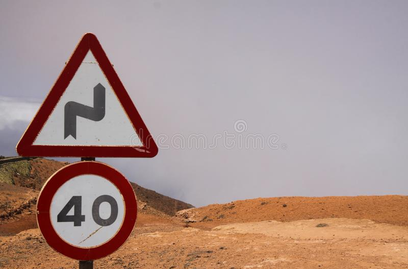 Mirador del Rio - Lanzarote:  Close up of Speed limit 40 sign and warning for curves signs above clouds on dry mountain Focus on royalty free stock image