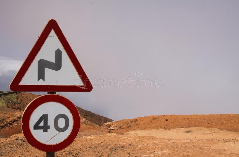 Mirador del Rio, Lanzarote -: Zamyka w górę prędkości ograniczenia 40 ostrzeżenia dla krzywa znaków nad chmury na suchej halnej o obraz royalty free