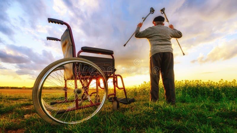 Mirakelåterställning: Gamala mannen får upp från rullstolen och lönelyfthänder upp royaltyfri bild