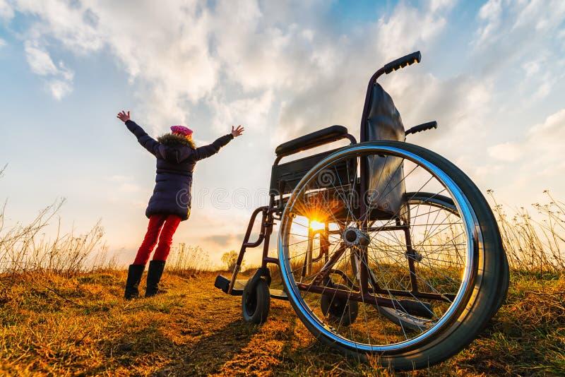 Mirakelåterställning II: unga flickan får upp från rullstolen och lönelyfthänder upp royaltyfria bilder