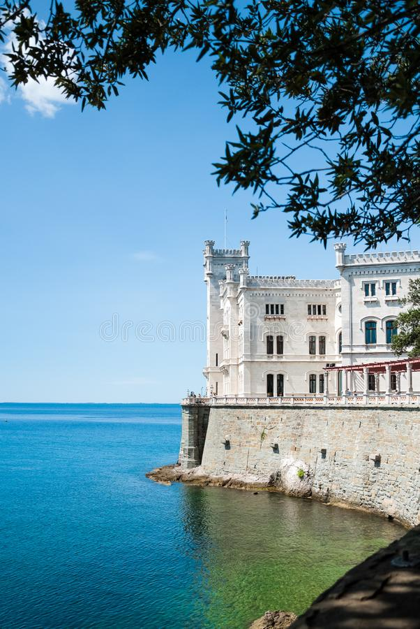 Miramare castle facing the gulf waters shot from aside and under an olive twig. Miramare castle in eclectic style, home of Austian archduke and Mexican emperor stock photos