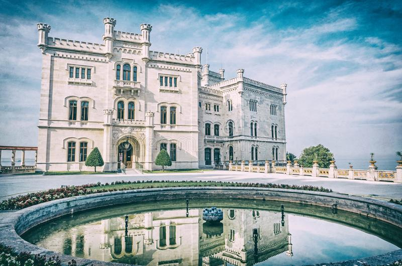 Miramare castle near Trieste, analog filter. Miramare castle is mirrored in fountain, northeastern Italy. Travel destination. Beautiful architecture. Analog stock photos