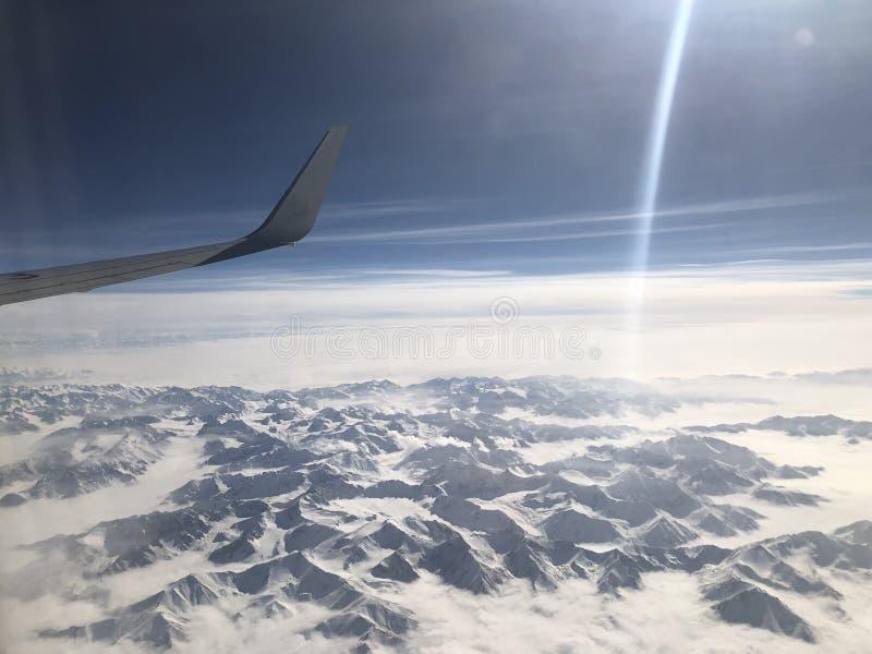 Mirando abajo del cielo, de las montañas cubiertas con nieve y del blanco se apilan fotos de archivo libres de regalías