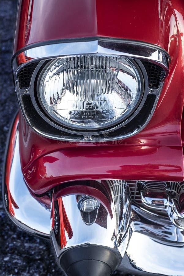 Mirando hacia abajo los faros cromados delanteros y el parachoques 1957 chevy aire clásico coche del músculo del cielo azul fotografía de archivo