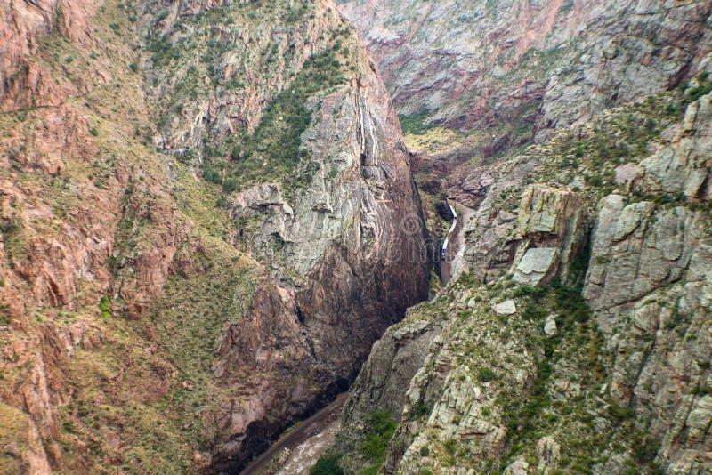 Mirando manera abajo el río Arkansas y el tren que corren al lado de él en la garganta real en Colorado imagenes de archivo