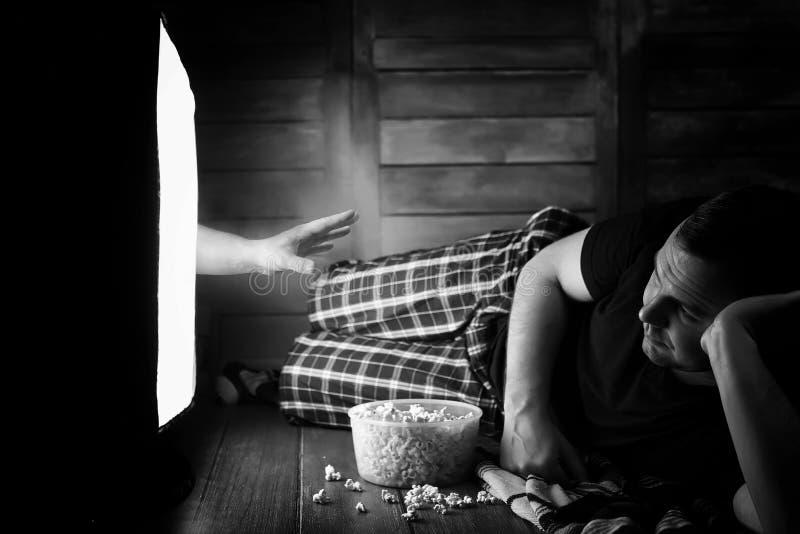 Mirando un horror en la TV blanco y negro imagen de archivo libre de regalías